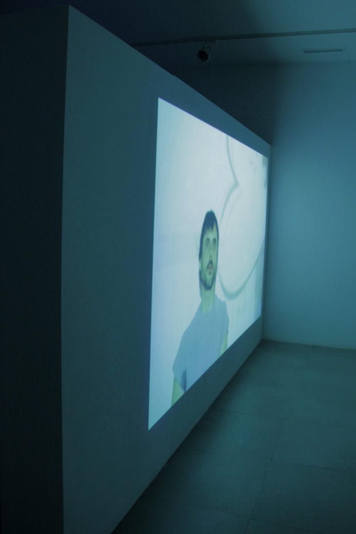 """Damià Jordà """"Rituales de consumo"""" (fotografía de la exposición, en la que vemos uno de los vídeos interpretados por Rubén Mira). Imagen cortesía de la galería."""
