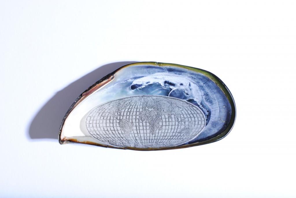 """Anna Bella Geiger, """"Sobre nácar com onda"""". (2014. Concha marina y mapamundi en plomo. Fotógrafo: Ruber Seabra). Imagen cortesía de la galería."""