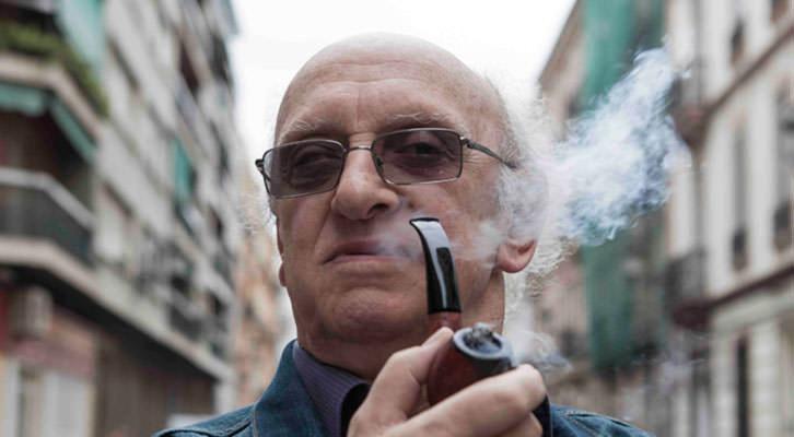 El escritor griego Petros Márkaris, con su pipa, en el barrio de Ruzafa en Valencia. Fotografía: Santiago Carrión.