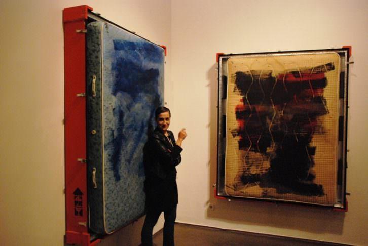 Rebeca Plana, entre dos de sus obras, en La Gallera. Imagen cortesía del Consorcio de Museos de la Generalitat Valenciana.