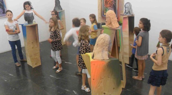 Niños del taller de la galería Luis Adelantado rodeando las esculturas de Folkert de Jong.
