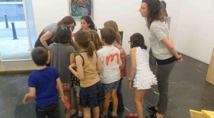 Olga Adelantado, rodeada de niños, ante la atenta mirada de Isabel Puig en el taller para pequeños de la galería Luis Adelantado.