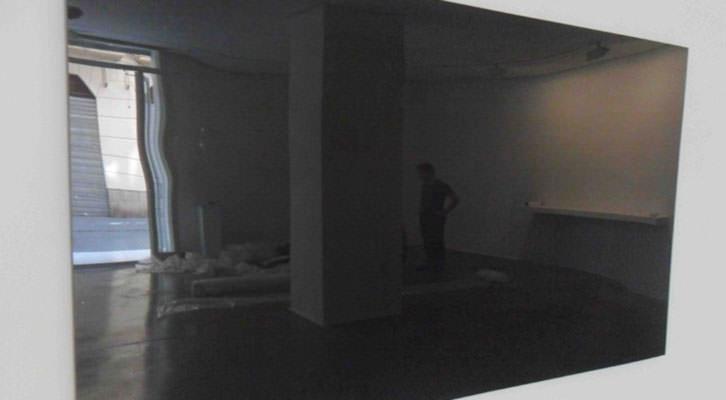 Pantalla espejo tras la cual se ocultan periódicos con noticias de crímenes, obra de Casey Tang en la galería Charpa de Valencia.