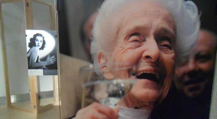 Fotografía de Rita Levi-Montalcini, sonriente, en la exposición 'Trencant barrees. Dones i ciències' que acoge el Palau de Cerveró.