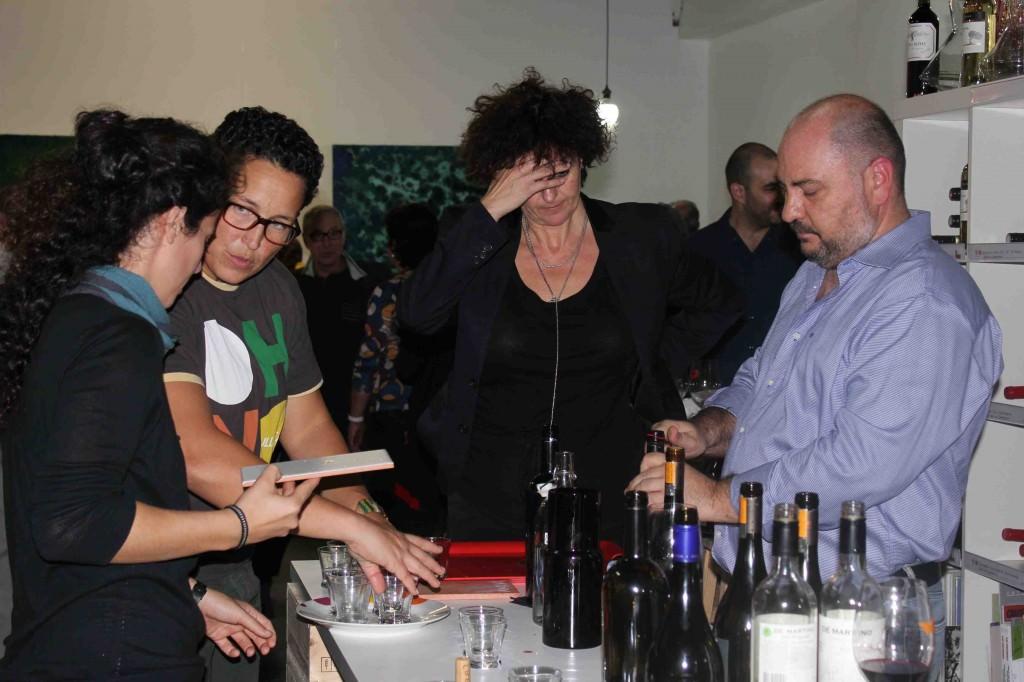 Rosa Guillem, responsable de Espacio 40, se echa las manos a la cabeza, mientras José Antonio Ruiz, de Vinos de Chile, abre una botella durante la inauguración de la exposición de Iñaki Torres.