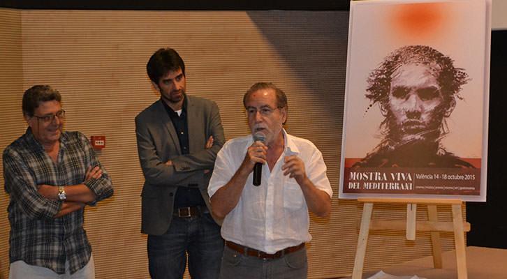 Manuel Boix, micrófono en mano, ante su cartel para Mostra Viva 2015, en presencia de Vicent Tamarit (izquierda) y José Luis Moreno (centro). Imagen cortesía de Filmoteca de CulturArts.