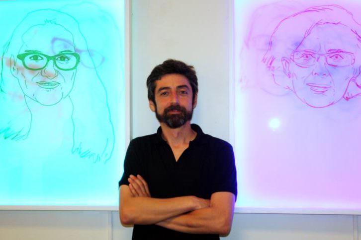 Javier Marisco ante sus obras LED de Mónica Oltra y Manuela Carmena, en la galería Alba Cabrera. Cortesía del autor.