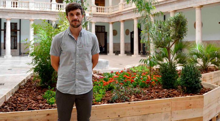 Juanli Carrión delante de su instalación artística. Imagen cortesía de La Nau.