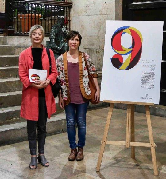 Marisa Gallén y Carmina Ibáñez junto al cartel diseñado por ellas. Imagen cortesía de las autoras.