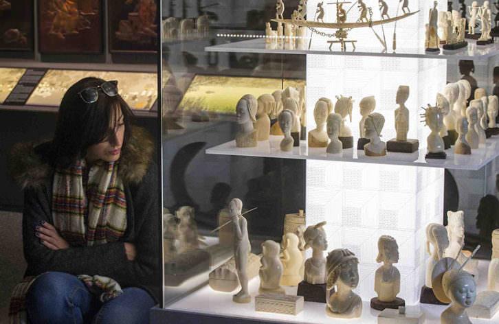 Una joven observa algunas de las pieza de la exposición Doctor Carsí, supongo? Fotografía de Raquel Abulaila cortesía del Museu Valencià d'Etnologia.