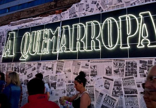 Imagen del logotipo de cabecera del periódico noir 'A Quemarropa' sobre un collage mural ubicado en el recinto del festival. Fotografía cortesía de los organizadores.