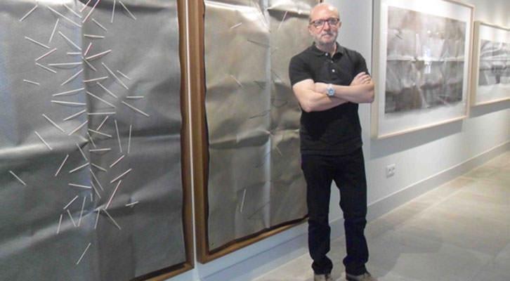 Sebastián Nicolau delante de algunas de sus obras en la galería Shiras.