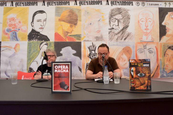 El escritor Vicente Marco y el periodista José Antequera, de la revista GURB, en un instante de la presentación de 'Ópera Magna' en la carpa 'A quemarropa', durante la XXIX Semana Negra de Gijón. Fotografía: Jose Ramón Alarcón.