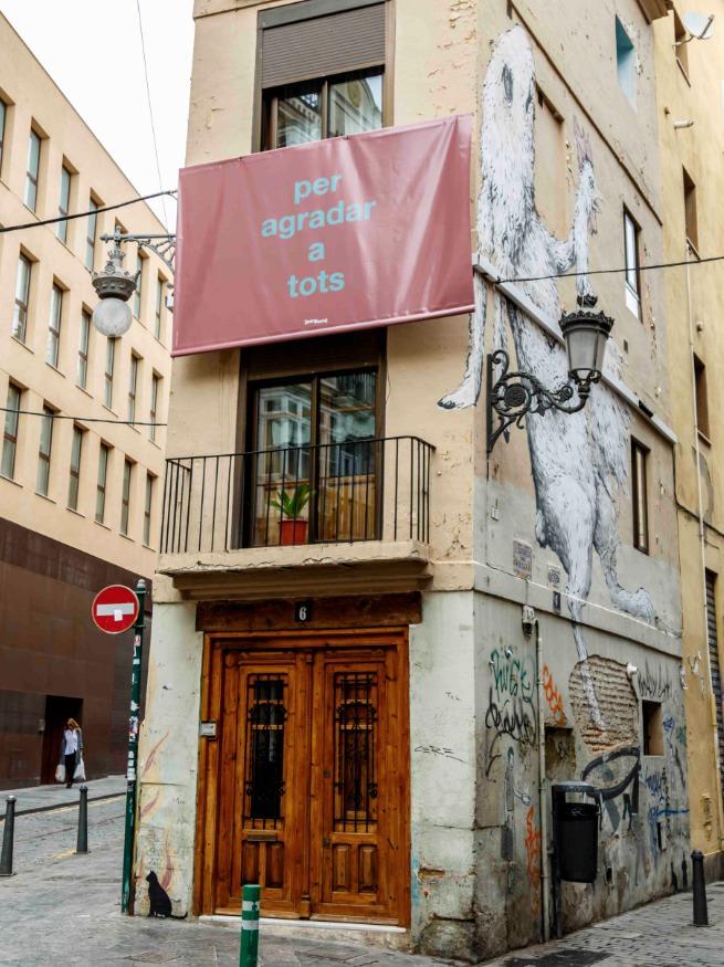 Obra de Fernando Baena colgada en un balcón entre la Calle Alta y la Calle Baja de Valencia. Foto de Enrique Miravalls por cortesía de Intramurs.