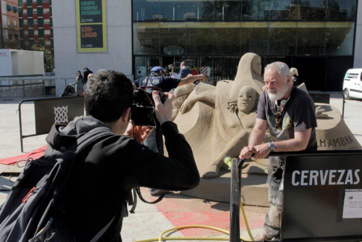 Dale Murdock junto a su escultura de arena. Imagen cortesía de Rambleta.