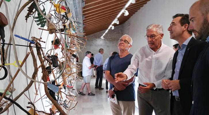 Pepe Gimeno, en el centro, de blanco, dando explicaciones de su obra.