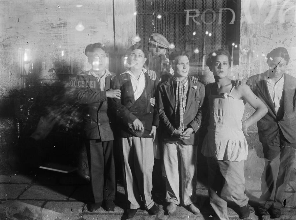 Imagen de 'Travestidos en una calle, vistos a través del vidrio de un bar, en el distrito 5, conocido popularmente  como el barrio Chino, en Barcelona', de Gabriel Casas. Fotografía cortesía de Núria Casas i Formiguera y Archivo Nacional de Catalu ña.