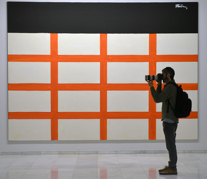 Un joven fotografiando junto a la obra de Günther Förg en la exposición Arte contemporáneo (1984-2010). Imagen cortesía de Fundación Bancaja.