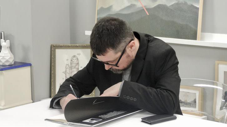 Pablo Amargo firmando un ejemplar de su libro, durante la entrevista con motivo de su exposición 'Cats are paradoxes', en Pepita Lumier. Foto: Javier Martínez