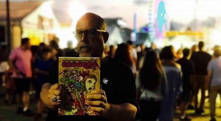 El escritor Jesús Palacios posa con un ejemplar de 'Eroguro. Horror y erotismo en la cultura popular japonesa', de Satori Ediciones, en plena XXXI Semana Negra de Gijón. Fotografía: Jose Ramón Alarcón.