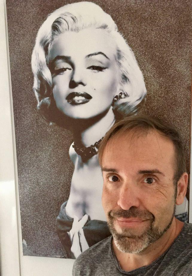 Javier Lacomba junto a un retrato de Marilyn Monroe. Imagen cortesía del autor.