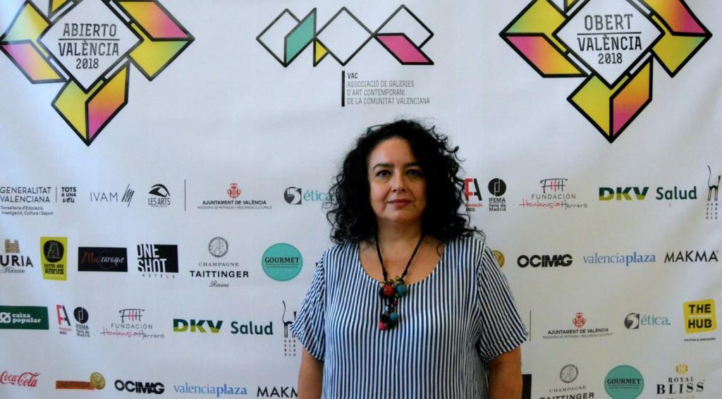 Begoña Martínez, responsable de la Galería Aural, delante del cartel de Abierto Valencia. Foto: Merche Medina.