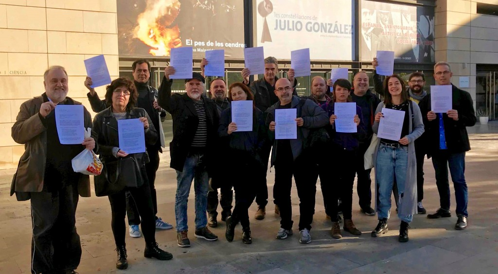 Diversos miembros de AVVAC muestran la misiva firmada por la presidenta de la Unión de Artistas Contemporáneos de España (UNIÓN_AC) a las puertas del IVAM. Fotografía cortesía de la asociación.
