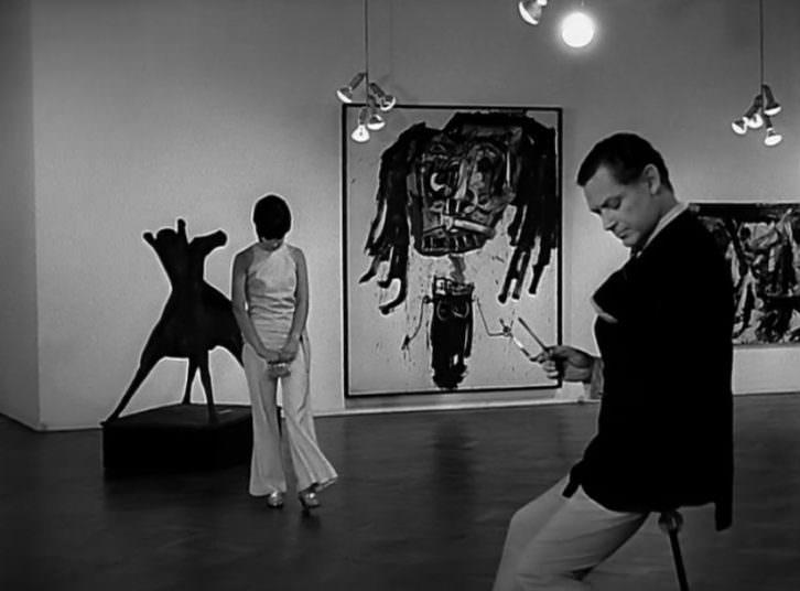 Fotograma de 'La boutique', de Luis García Berlanga, con la obra 'Retrato imaginario de Brigitte Bardot, al fondo.